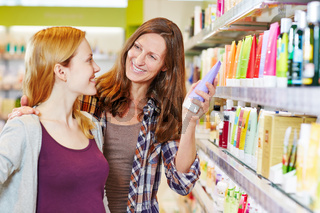 Mutter und Tochter kaufen Kosmetik in Drogerie