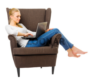 Young girl in jeans on chair with laptop isolated