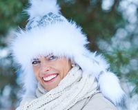 Lachende Frau mit Fellmütze im Winter