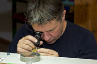 Watchmaker checking a part of a wristwatch
