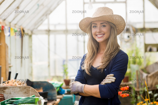 Pretty blonde smiling in greenhouse