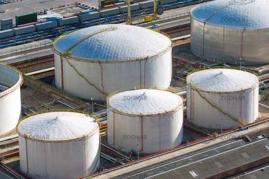 White gas storage tanks seen in a harbour