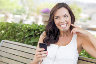 Smiling Young Adult Female Texting on Cell Phone Outdoors