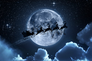 Santa flying in his sleigh against a full moon background with stars and clouds.