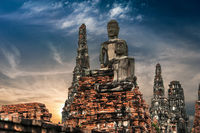 Asian religious architecture. Ancient sandstone sculpture of Buddha at Chai Watthnaram temple ruins under sunset sky. Ayutthaya, Thailand