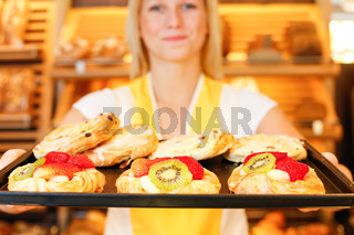 Bakery shopkeeper with tablet of cakes