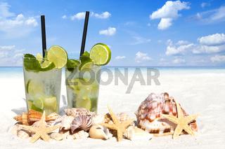 Eiskalter Mojito Cocktail und Muscheln am Sandstrand