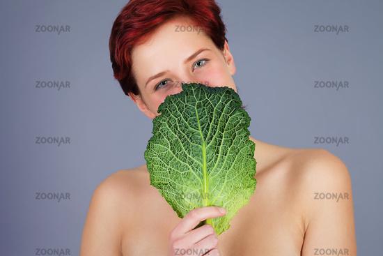 woman hiding behind savoy cabbage leaf