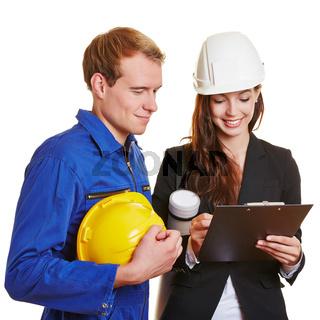 Architektin unterschreibt Rechnung vom Handwerker