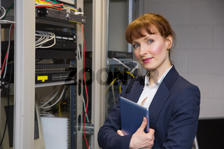 Pretty technician smiling at camera beside open server holding tablet pc