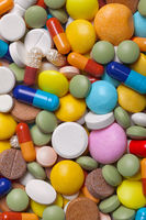 Pile of colorful medications tablets - medical background