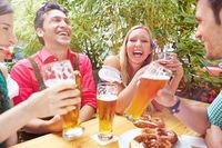 Lachende Freunde im Biergarten beim Oktoberfest
