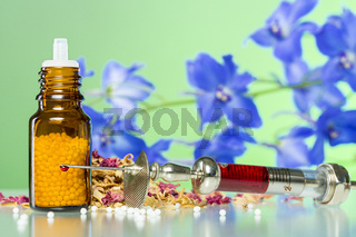 still life with homeopathy globule, syringe with blood, some spices and flowers