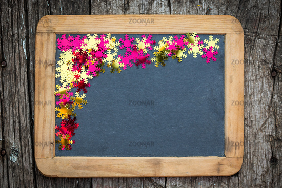 Christmas frame of confetti on blackboard