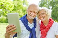 Zwei Senioren machen Selfie mit Tablet PC
