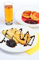 food of crepes, cheesecakes with berry sause and glass of juice.