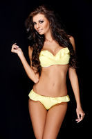Tanned sexy brunette posing in yellow swimsuit