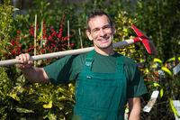 Farmer or gardener posing with shovel in garden