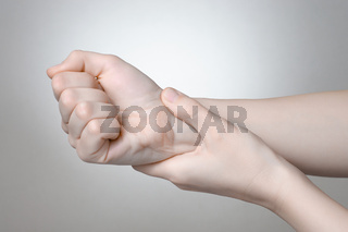 A young woman holding her painful wrist