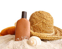 Straw hat with towel and suntan lotion on white