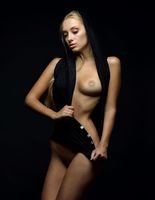 Beautiful naked blonde woman in a black blouse posing in a dark Studio