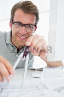 Smiling young man using compass on design