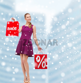 elegant young woman with shopping bags in city