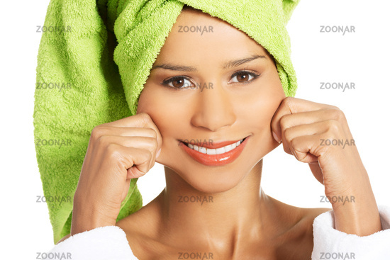 Attractive woman wrapped in towel, holding her mouth in a smile.