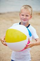 Kind mit Wasserball am Strand