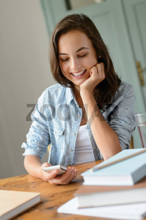 Smiling teenage girl looking mobile phone home