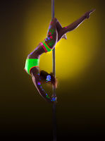 Graceful pole dancer posing under UV light