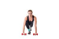 Beautiful athlete squatting with dumbbells