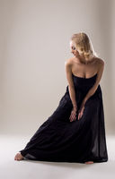 Attractive blonde in black dress posing at camera