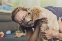 young woman hugging her little dog