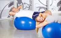 Senioren machen Sit-Ups im Fitnesscenter