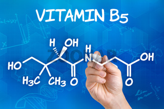 Hand with pen drawing the chemical formula of Vitamin B5