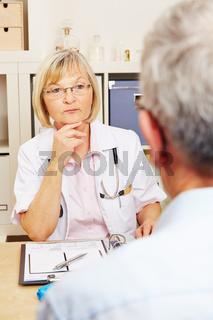 Ärztin hört Patient zu in Sprechstunde
