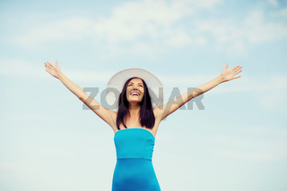 girl with hands up on the beach
