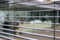 horizontal blinds in front of a large glass fronta