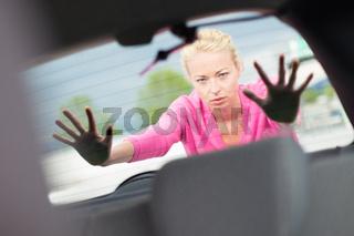 Woman pushing a car.