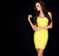 Sexy slim brunette posing in yellow dress