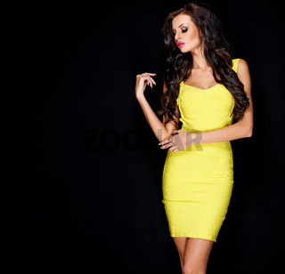 Sexy slim brunette posing in yellow dress