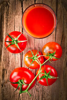 Tomato juice in glass and fresh organic tomatoes
