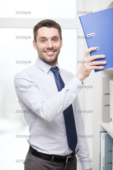 handsome businessman picking folder at office
