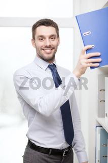 handsome businessman picking folder at office