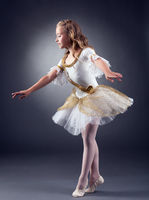 Cute little ballerina dancing in studio