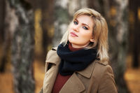 Happy blond woman in autumn forest