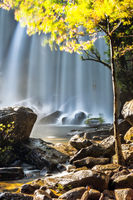 Sunny day at tropical rain forest landscape with flowing blue water of Kulen waterfall in Cambodia