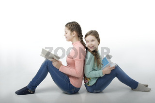 Little girls read books back to back isolated on white