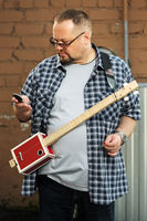 Man with a cigar box guitar looking at cell phone